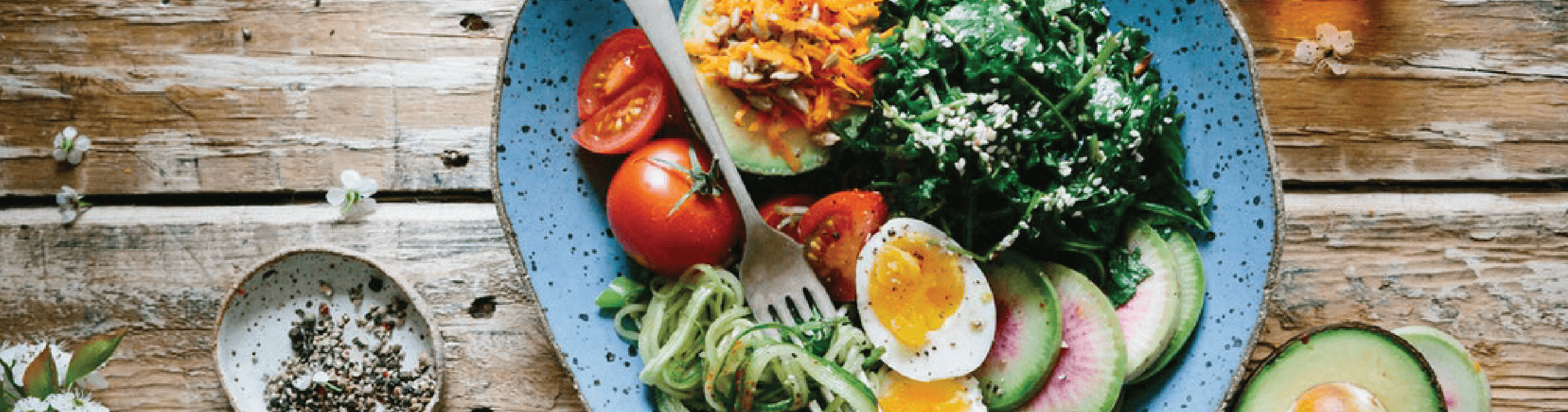 prato de salada com ovos, rúcula, acabate, cenoura, tomate em uma mesa de madeira com temperos em volta.