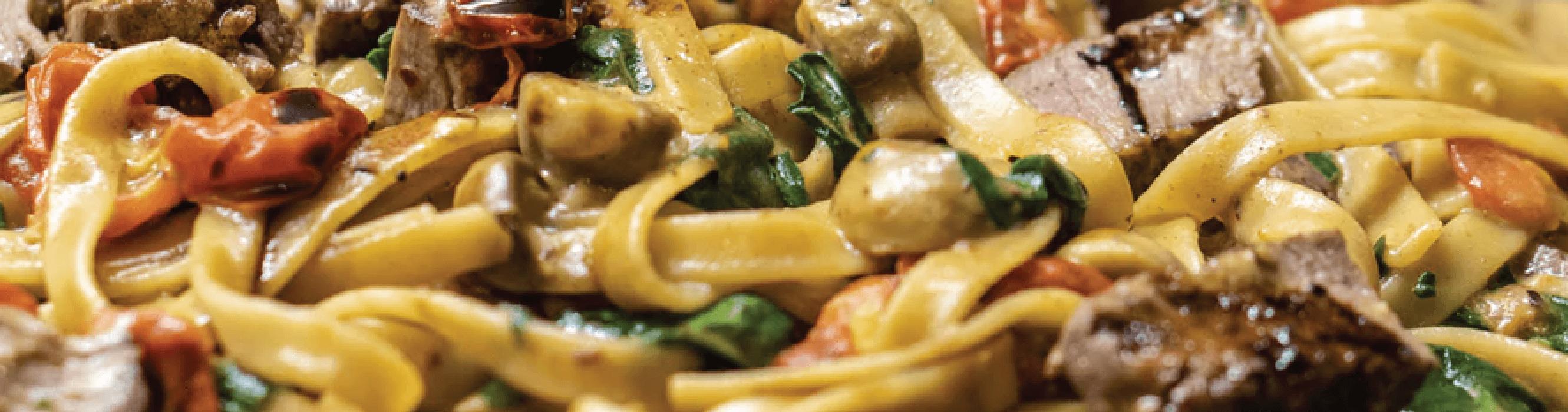 prato de macarrão com pedaços de carnes, legumes e vegetais.