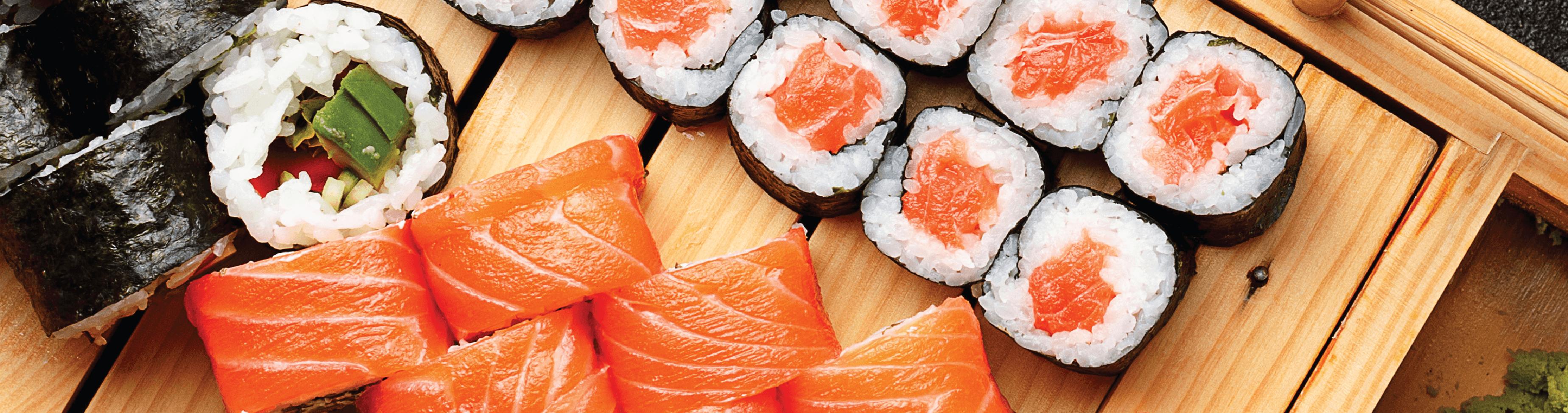 mesa de madeira com peças de sushis e sashimis - comidas típicas do japão